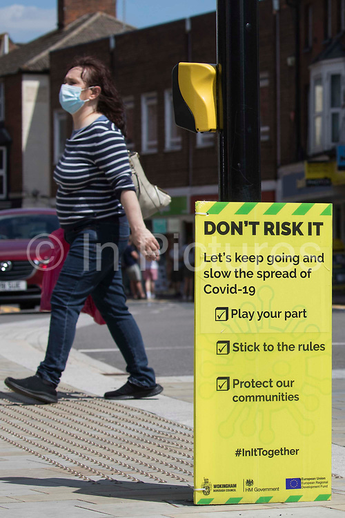 A local resident wearing a face covering passes a Covid-19 public information display amid rising local concern regarding the spread of the Delta variant on 8th June 2021 in Wokingham, United Kingdom. Surge testing has been introduced in some local postcodes after a small number of cases of the Delta variant first identified in India were confirmed in the Wokingham area.