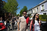 People heading to and from the market pass past the colourfully painted houses on Portobello Road in Notting Hill, West London, England, United Kingdom. People enjoying a sunny day out hanging out at the famous Sunday market, when the antique stalls line the street.  Portobello Market is the worlds largest antiques market with over 1,000 dealers selling every kind of antique and collectible. Visitors flock from all over the world to walk along one of Londons best loved streets.