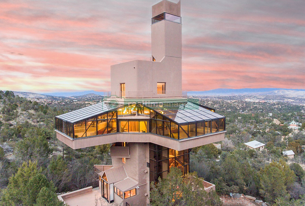 """April 3, 2017 - inconnu - This stunning high-rise home is the world's tallest house for a single family.The towering 124 foot / 37.8 metre high structure in the US Wild West state of Arizona, is aptly named the Falcon Next.It's top floor offers incredible panoramic views of the dessert landscape and is now on the market for $1.5million USD / €1.4 million Euros / £1.19 million GBP.The a 576 square metre / 6,200-square-foot home near Thumb Butte in Prescott, Arizona, was designed by Phoenix architect Sukumar Pal.The ten-story home has three bedrooms, four bathrooms, glass ceilings and affords views for over 120 miles to the San Francisco Peaks.It also has a hydraulic elevator as well as a unique energy system that cools the home in the summer and heats it during winter. Listing agent Frank Aazami of Russ Lyon Sotheby's International Realty said the home was a """" architectural rarity.""""He said it was built with holistic living and green techbologies and efficiencies in mind including solar power.It comes with 1.08 acres of land yet is just a 10 miniute fdrive from the nearest town.The central level is a 2,000 square foot / 186 square metre nearly all glass space with two beds, two baths, kitchen, and great room. The elevator provides access from the garage level to the sixth floor. A spokesman for Russ Lyon Sotheby's International Realty said:"""" With minimal energy consumption, a small footprint, and utilizing natural elements to heat and cool the home free from cost, this is truly an architectural and engineering treasure."""" # UNE MAISON HAUT PERCHEE A VENDRE (Credit Image: © Visual via ZUMA Press)"""