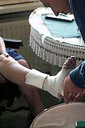 Nederland, Nijmegen, 27-3-2003Huisarts op visite bij oudere patient verbindt een wond aan het been. Gezondheidszorg, basiszorg, eerstelijns hulpverlening.Foto: Flip Franssen