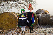 Tamara, member of the 'Schwälmer Tanz- und Trachtengruppe' is wearing an original traditional bridal costume in Schreckshausen, Hesse, Germany on December 4, 2016.<br /> <br /> Groom: Paul<br /> <br /> It took 3 hours to dress Tamara in the original costume. All ribbons on the head and back are pinned together with about 200 pins. The flowers on the arms stand for the wish of having many kids. The Schwälmer Tracht (Traditional Costume of the Schwalm area) is the only one in Germany where the groom also wore an elaborate headpiece.<br /> Only pristine women were allowed to wear the bridal crown.<br /> <br /> This is part of the series about Traditional Wedding Gowns from different regions of Germany, worn by young members of local dance groups and cultural associations that exist to preserve and celebrate the cultural heritage. The portraiture series is a depiction of an old era with different social values and religious beliefs in an antiquated civil society with very few of those dresses left.