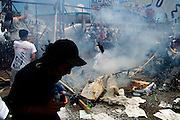 10 SEPTEMBER 2003 - CANCUN, QUINTANA ROO, MEXICO: A protestor opposed to the World Trade Organization runs past a bonfire at the fence separating the downtown area from the hotel zone in Cancun, Quintana Roo, Mexico during a protest against the WTO. Tens of thousands of people opposed to the WTO have come to this Mexican resort city to protest the 5th Ministerial meeting of the World Trade Organization. The WTO meetings are taking place in the hotel zone of Cancun, about 10 miles from the protestors.  PHOTO BY JACK KURTZ
