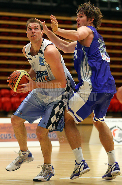 PERTH, AUSTRALIA - JULY 16: Troy Thomson of the Tigers drives to the basket against Ben Purser of the Hawks during the week 18 SBL game between the Perry Lakes Hawks and the Willetton TIgers at The State Basketball Center on July 16, 2011 in Perth, Australia.  (Photo by Paul Kane/Allsports Photography)