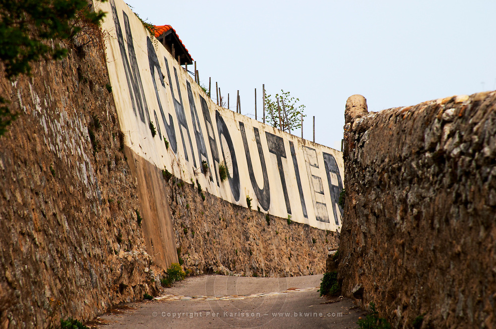 A narrow alley road on the Hermitage hill with M Chapoutier painted in black on white on a stone wall. Tain l'Hermitage, Drome, Drôme, France, Europe
