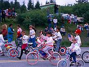Yakutat Summer School kids, Tlingit and Caucasian, bicycling in Fourth of July Parade, Yakutat, Alaska.