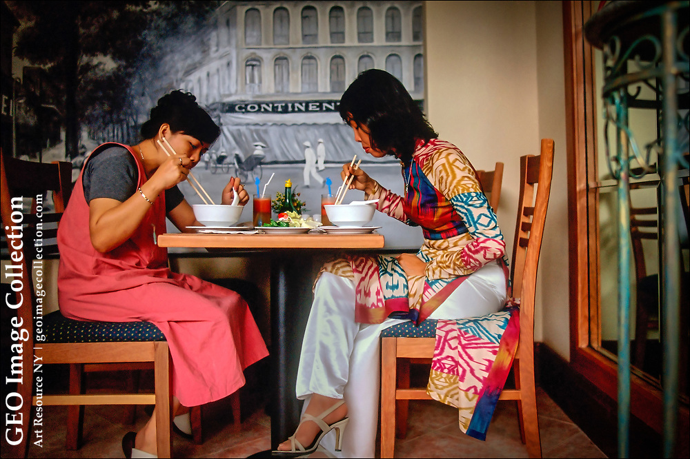 """Vietnamese women, one dressed in traditional """"ao dai"""" a silk tunic with pants (right), eat noodle soup called Pho at a restaurant in Ho Chi Minh City. Pho is made of broth, rice noodles, herbs, and meat or tofu. In the background is a painting of the former Continental Palace Hotel, a relic of French colonial days, and its open-sided terrace called the """"the Continental Shelf"""" by legions of journalists, writers, and spies."""