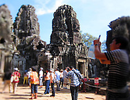 Tourists photographing and admiring the ancient Angkor ruins, Siem Reap, Cambodia, Southeast Asia
