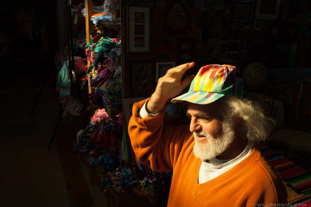 """Roger Josephson poses in a room he calls his """"color zone"""" at his residence in The Plains, Ohio, Nov. 11, 2011. Josephson, who creates art in a variety of media, first started doing tie dye as a summer job while studying economics over 30 years ago and still gets requests for hats even though he hasn't made them in over a decade."""