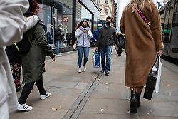 © Licensed to London News Pictures. 19/10/2020. Manchester, UK. A couple wearing face masks walks down Market Street, Manchester. Manchester is on the verge of a Tier 3 lockdown Photo credit: Kerry Elsworth/LNP