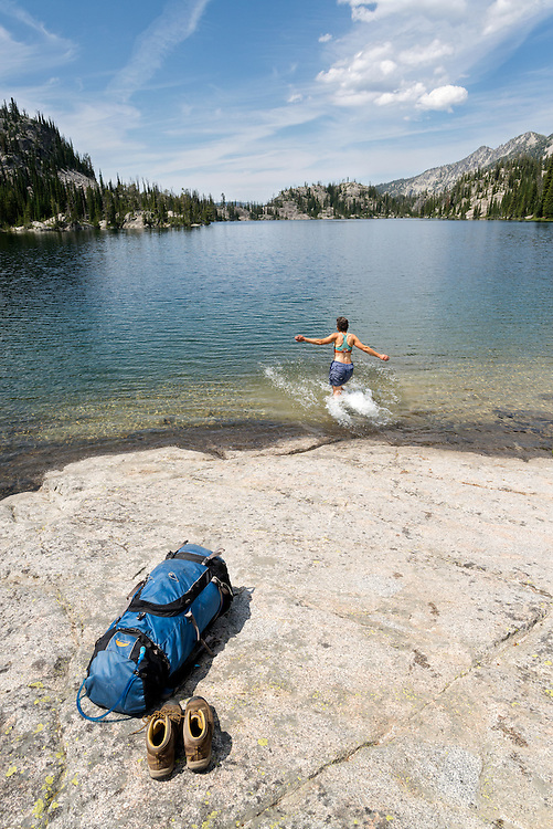 Backpacker going for a swim in a lake high in Oregon's Wallowa Mountains.