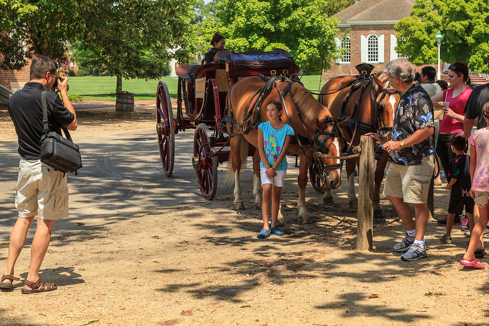 A girl is photographed with a horse carriage at Colonial Williamsburg, VA.
