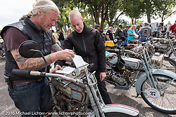 Thomas Trapp, owner of the Harley-Factory Frankfurt dealership in Germany adjusts his roll chart with the afternoon directions on his 1916 Harley-Davidson with his son Eric after te lunch stop in an Alamosa park during the Motorcycle Cannonball Race of the Century. Stage-10 ride from Pueblo, CO to Durango, CO. USA. Tuesday September 20, 2016. Photography ©2016 Michael Lichter.