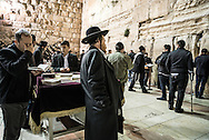 Evening prayers at the Western Wall. Wooden tables often covered in velvet embroidered draps are put next to the wall and contain prayers book (siddur) containing a set order of daily prayers. Worshipper can borrow them.
