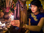 28 OCTOBER 2015 - YANGON, MYANMAR: A woman lights candles while praying at a statue of the Buddha during observances of Thadingyut at Botataung Pagoda in Yangon. Botataung Pagoda was first built by the Mon, a Burmese ethnic minority, around the same time as was Shwedagon Pagoda, over 2500 years ago. The Thadingyut Festival, the Lighting Festival of Myanmar, is held on the full moon day of the Burmese Lunar month of Thadingyut. As a custom, it is held at the end of the Buddhist lent (Vassa). The Thadingyut festival is the celebration to welcome the Buddha's descent from heaven.    PHOTO BY JACK KURTZ