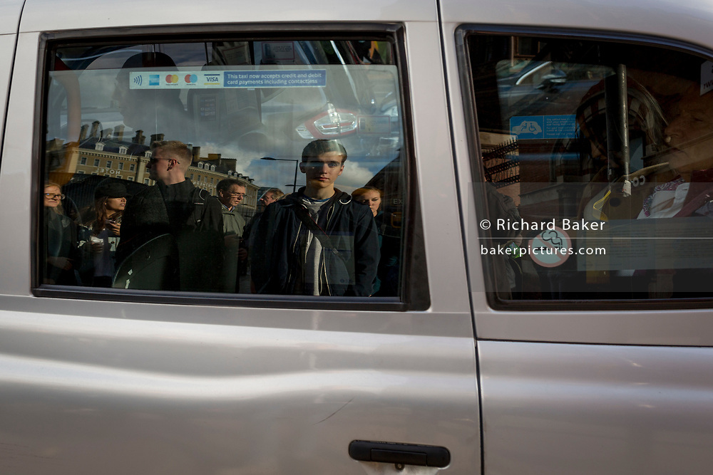 A nineteen year-old man and other pedestrians are reflected in the window of a passing taxi cab in Kings Cross, on 22nd October 2017, in London, England.