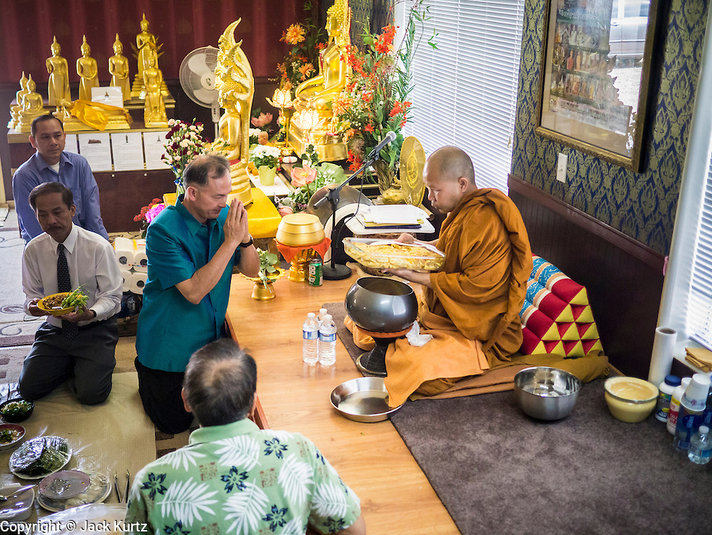 """11 MARCH 2012 - CHANDLER, AZ:      The Abbot at Wat Pa in Chandler, AZ, collects food in the """"bot"""" or ordination hall during Makha Bucha day services Sunday. Magha Puja (also spelled Makha Bucha) Day marks the day 2,500 years ago that 1,250 Sangha came spontaneously to see the Buddha who preached to them on the full moon. All of them were """"Arhantas"""" or Enlightened Ones who had been personally ordained by the Buddha. The Buddha gave them the principles of Buddhism, called """"The Ovadhapatimokha."""" Those principles are: to cease from all evil, to do what is good, and to cleanse one's mind. It is one of the most important holy days in the Theravada Buddhist tradition. At the temple, people participate in the """"Tum Boon"""" (making merit by listening to the monk's preaching and giving a donation to the temple), the """"Rub Sil"""" (keeping of the Five Precepts including the abstinence from alcohol and other immoral acts) and the """"Tuk Bard"""" (offering food to the monks in their alms bowls). It is a day for veneration of the Buddha and his teachings. It's a legal holiday in Thailand, Laos, Cambodia and Myanmar (Burma).    PHOTO BY JACK KURTZ"""