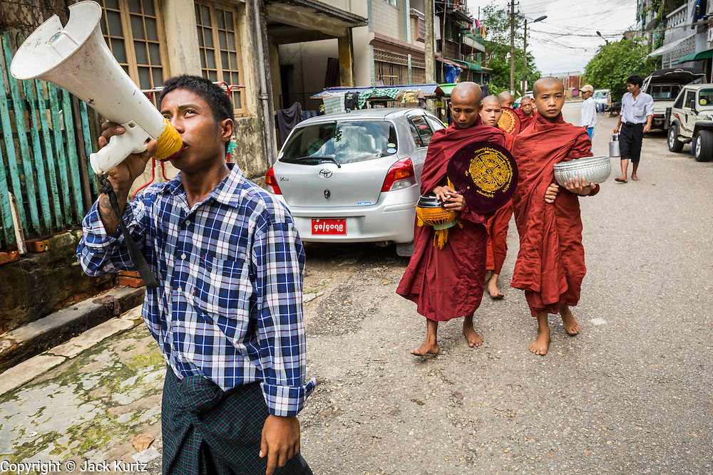 """13 JUNE 2013 - YANGON, MYANMAR:   A man with a bullhorn announces Buddhist monks walking down a street in Yangon soliciting alms and donations. Most men in Myanmar join the """"Sangha"""" (clergy) at least once in their life. Some stay monks for just a few weeks, others for year and a few make it a life time commitment. Yangon, formerly Rangoon, is Myanmar's commercial capital and used to be the national capital. The city is on the Irrawaddy River and has a vibrant riverfront.  PHOTO BY JACK KURTZ"""