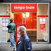 Nederland, Amsterdam , 16 juli 2012..De werkeloosheid onder jonge allochtonen schijnt erg hoog te zijn. In ieder geval een stuk hoger dan onder autochtonen jongeren..Op de foto een allochtone jonge man bekijkt vacatures op een bord van uitzendbureau Tempo Team op het Osdorpplein..Foto:Jean-Pierre Jans