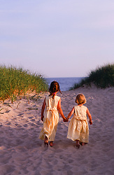 two little girls in pretty yellow dresses walking on the sand to the ocean in East Hampton, NY