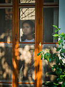 """05 NOVEMBER 2015 - YANGON, MYANMAR: A woman peers out the front door to the home of Aung San Suu Kyi. She lived in house arrest here for more than 15 years. Suu Kyi is now contesting a national election in Myanmar and hosted a press conference at her home. During the press conference, which lasted 90 minutes, Aung San Suu Kyi, the leader of the National League for Democracy (NLD), said that if the NLD won the election she would serve """"above"""" the President. When questioned about the Rohingya crisis in western Myanmar, a reporter called the situation """"dramatic"""" and Suu Kyi replied the entire country is in a """"dramatic situation"""" and the problems of the Rohingya should not be """"exaggerated."""" She said the """"great majority of our people remain as poor as ever."""" She also said the NLD would make a """"fuss"""" if election results were """"suspicious."""" Citizens of Myanmar go to the polls Sunday November 8 in what is widely viewed as the most democratic and contested election in Myanmar's history. The NLD is widely expected to win the election.   PHOTO BY JACK KURTZ"""