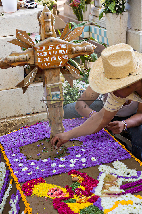 People decorated a graves with elaborate floral pedal tapestries in honor of the deceased at the San Antonino Castillo cemetery during the Day of the Dead Festival known as Día de Muertos on November 3, 2013 in San Antonino Castillo Velasco, Oaxaca, Mexico.