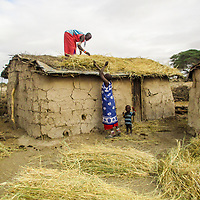 Mrasha, helping her friend Narasha to thatch one of their homes as her little one smiles for the camera.