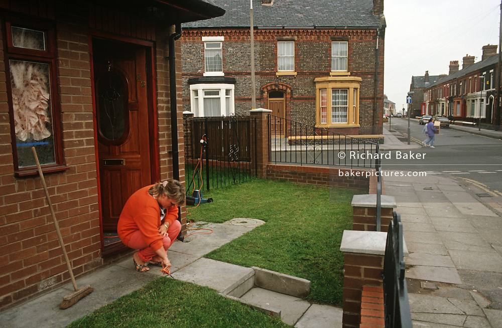 A house-proud housewife trims her lawn with a pair of scissors in new housing on a terraced Liverpool street.