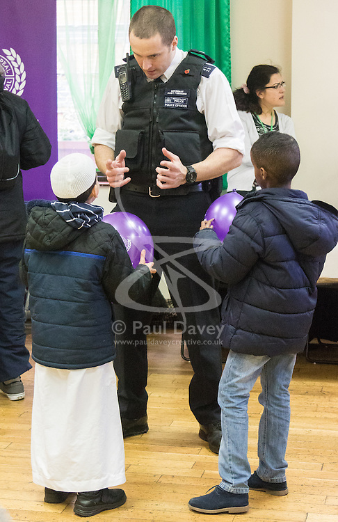 """Finsbury Park Mosque, London, February 7th 2016. Local copper Sergeant Andy Perversi explains his job to two young boys as part of a Visit My Mosque initiative by the Muslim Council of Britain to show non-Muslims """"how Muslims connect to God, connect to communities and to neighbours around them"""".<br /> . ///FOR LICENCING CONTACT: paul@pauldaveycreative.co.uk TEL:+44 (0) 7966 016 296 or +44 (0) 20 8969 6875. ©2015 Paul R Davey. All rights reserved."""