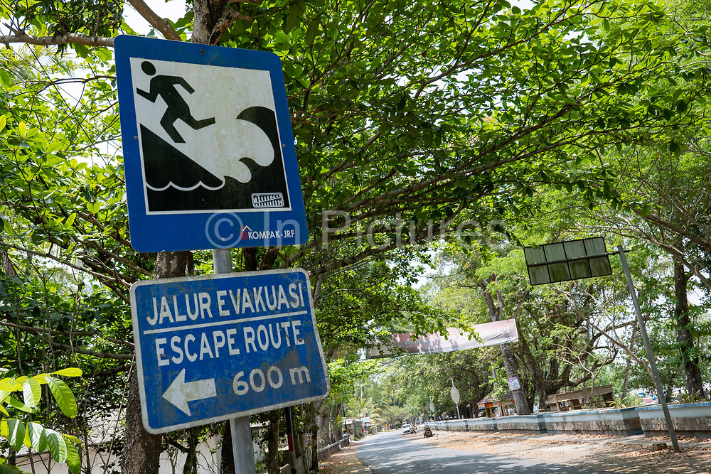 A tsunami warning sign post showing escape route directions at the fishing village of Batu Karas on the 27th October 2019 in West Java in Indonesia.