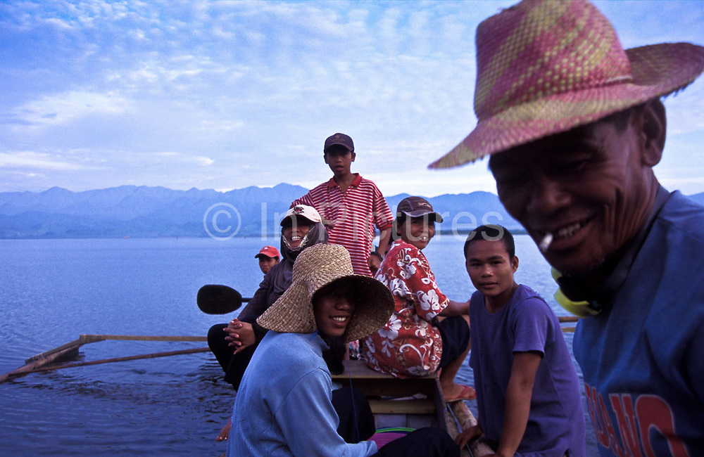 A group of fishermen and women go out in a large banka to fish with nets, Gumacas bay, Aurora, Philippines