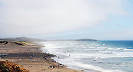Wide-shot of waves rolling into Salmon Creek Beach on a warm summer day
