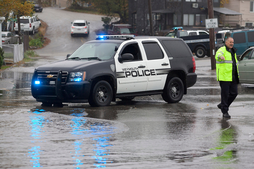 Weymouth, MA 10/29/2012<br /> A police officer directs traffic as water flows over the seawall on Wessaugusett Rd at Wittaumet Rd in Weymouth during Hurricane Sandy on Monday.