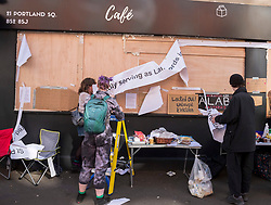 © Licensed to London News Pictures; 09/10/2021; Bristol, UK. People tear down a landlord's poster during a protest against gentrification and the closure of the Hidden Corner cafe and bookshop in St Pauls, a black owned business and QTPOC (queer and/or trans people of colour) friendly space, after the business' owners Sophia Khan and her partner Aaron Onuora were locked out of the premises by their landlord, Presman Ltd. The couple run Hidden Corner which stocks books including fiction, non-fiction and children's books, mostly by people of colour (POC) and queer authors, and has a cafe with affordable prices for the local St Pauls community and other disadvantaged groups. On 04 October Sophia went to open the cafe only to find the door locked with chains and a notice from the landlord saying they re-entered the property under a clause in the lease. Sophia says they have always paid the rent on time. Sophia has said they have had some recent difficulties with the landlord and were made to feel their business did not fit with the image the owner wanted to present to Airbnb guests who come to stay on the floors above. Photo credit: Simon Chapman/LNP.