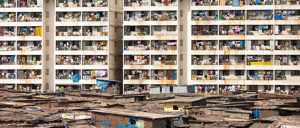 Slum housing and slum dwellers next to tenement apartment blocks in city of Mumbai, formerly Bombay, India. RESERVED USE.<br />