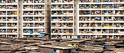 Slum housing and slum dwellers next to tenement apartment blocks in city of Mumbai, formerly Bombay, India. RESERVED USE.<br /> FINE ART PHOTOGRAPHY by Tim Graham