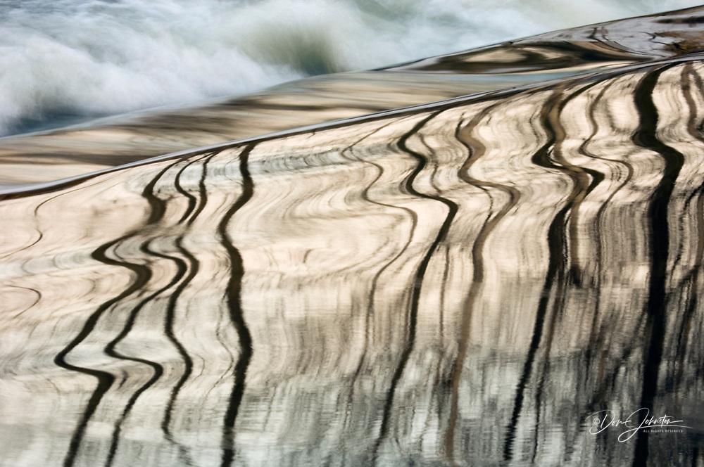 Distorted tree reflections in open water of Junction Creek flowing over dam, Sudbury, Ontario, Canada