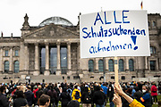 """A protester holds a banner reading """"Accept all those seeking protection"""" as people take part in a demonstration in front the Reichstag  building, seat of the German lower house of Parliament, the Bundestag in Berlin, Germany, August 17, 2021. About 1000 people gathered in front of the  under the call """"Airlift now! Create safe escape routes from Afghanistan!"""", the spontaneous event was organized by Seebrücke and several other human-rights organizations."""