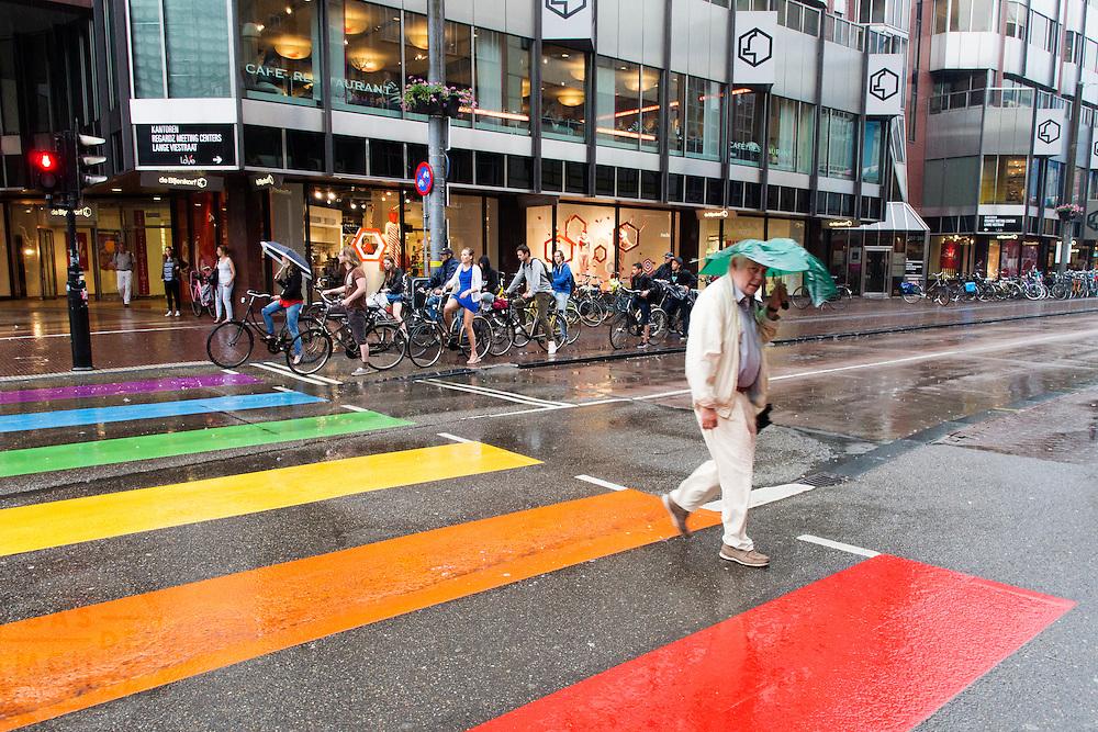 Een man steekt in de regen het zebrapad in de regenboogkleuren over in Utrecht. In de achtergrond wachten fietsers tot het verkeerslicht op groen gaat.<br /> <br /> A man is crossing the streets with rainbow colors in the rain in Utrecht. In the back cyclist are waiting for the traffic light to turn green.