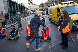 """© Licensed to London News Pictures. 25/10/2021. London, UK. A member of the public how said to IB protestors """"I hope you get cancer"""" continues to remonstrate. Insulate Britain climate change activists block traffic on Bishopsgate in the City of London. The group have restarted their actions to block motorways and major roads causing disruption in the week before the COP26 climate meeting in Glasgow on 31/10/2021. Photo credit: Ben Cawthra/LNP"""