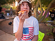 16 OCTOBER 2011 - PHOENIX, AZ: An Occupy Phoenix protester eats a slice of pizza at the protest site in Phoenix, AZ, Sunday. A supporter of the protest donated about 15 large pizzas to the protesters at dinner time Sunday. About 200 people continued the Occupy Phoenix protest in downtown Phoenix Sunday afternoon. The protest peaked Saturday afternoon at about 2,000 people. Nearly 50 people were arrested late Saturday night on misdemeanor trespassing charges when they tried to camp in a park near downtown and on Sunday the crowd dwindled to 200. Protesters hope to continue the protest through Monday by marching around downtown and picketing banks in the area.   PHOTO BY JACK KURTZ