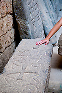 """Tripoli, Lebanon - September 7, 2010: A young woman's hand touches a stone slab in which a cross is carved, symbolizing """"the now"""" touching """"the past"""". Located at the citadel in Tripoli, the stone carving is probably from the Byzantine era."""