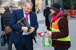 London, UK. 13th February, 2019. A man gives a donation to the strike fund in return for a strike-themed cup cake from a Public & Commercial Services (PCS) union member on a picket line outside the Department of Business, Energy and Industrial Strategy (BEIS) after outsourced workers walked out for their second day of strike action to demand the London Living Wage and an end to outsourcing.