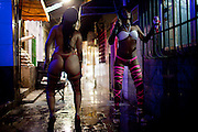 This photo taken May 4, 2011 shows sex workers dancing as they wait for customers at the Vila Mimosa prostitution zone in Rio de Janeiro, Brazil. <br /> <br /> Spelling the possible end of Vila Mimosa is a high-speed train the government wants to build to link Rio to Sao Paulo, as part of Brazil's Olympic proposal. The government is expected to open bidding to prospective builders July 29.