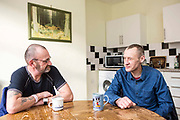 Ian and Rob sitting in their kitchen. They were both recently living on the streets of Peterborough.  With the help of Hope into Action he is now settled into safe and secure housing and is building connections with his family. Peterborough, Cambridgeshire. UK