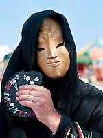 Magician performing behind a mask in a fair.