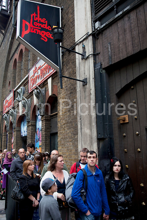 "Tourists queue up outside the London Dungeons at London Bridge. The London Dungeon is a popular London tourist attraction,[1] which recreates various gory and macabre historical events in a grimly comedic 'gallows humour' style, attempting to make them appealing to younger audiences. It uses a mixture of live actors, special effects and rides.Opening in 1974, it was initially designed as more a museum of ""horrible history"", but the Dungeon has evolved to become an actor-led, interactive experience."
