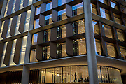 An employee with Bloomberg works beneath bold, modern architecture by Fosters + Partners in the company's new European headquarters on Cannon Street in the Square Mile, the heart of the capital's financial district, on 2nd October 2017, in the City of London, England. In October 2018 the building won the Riba Stirling prize for architecture. It is the world's most sustainable office and largest stone building in the City of London.