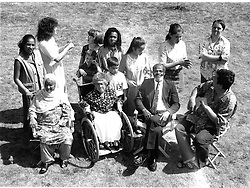 Large multiracial group standing together outdoors; including elderly woman who is wheelchair user; people with hearing impairments communicating through sign language & man with Downs Syndrome,