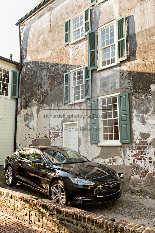 Tesla electric car parked outside a historic home on Church Street in Charleston, SC.