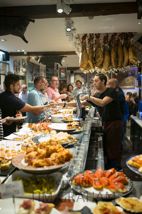 Diners and staff in pintxos tapas snack bar restaurant in San Sebastian, Donostia, in Basque Country, Spain
